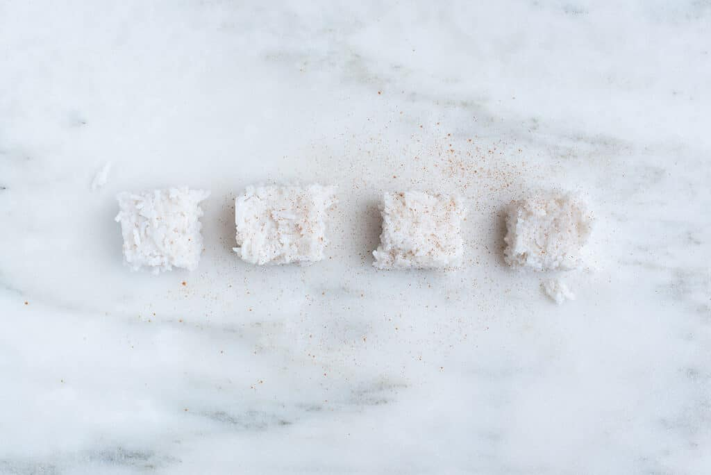 four squares of coconut milk rice, spiced with cinnamon, sitting on a countertop