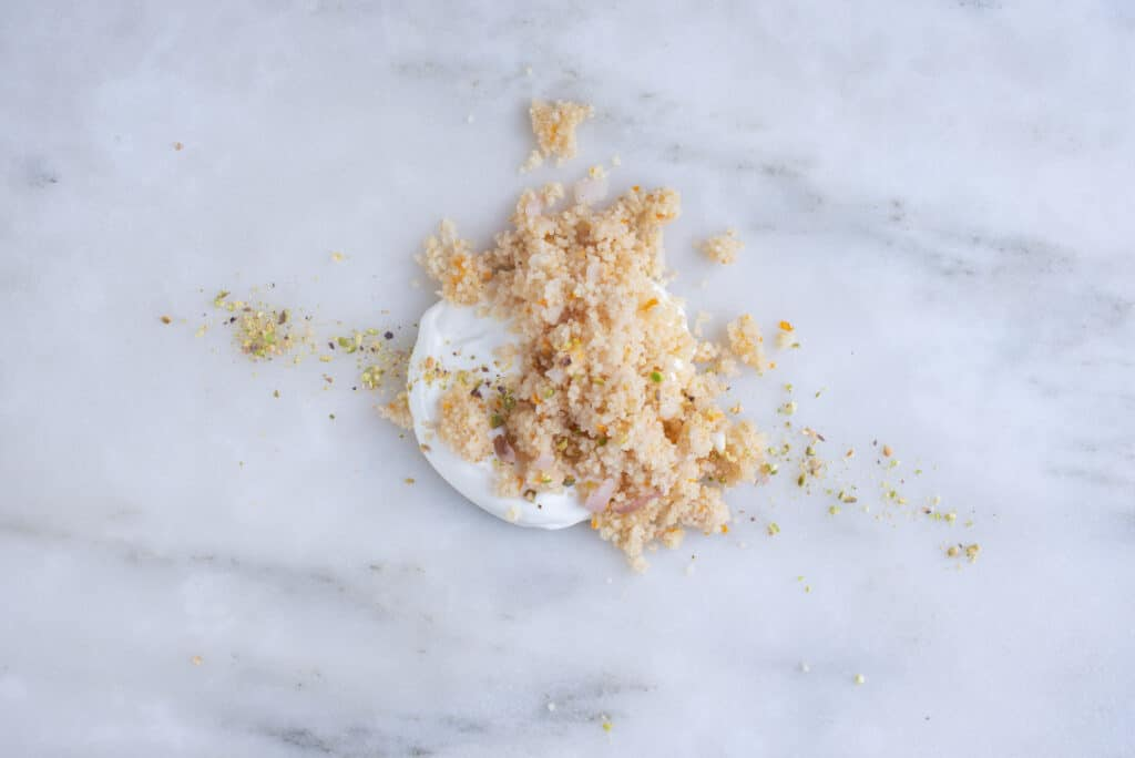 pile of couscous atop yogurt, sitting on a countertop