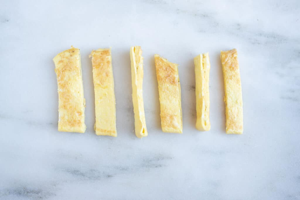 an omelet cut into strips on a white background for 6 month old babies