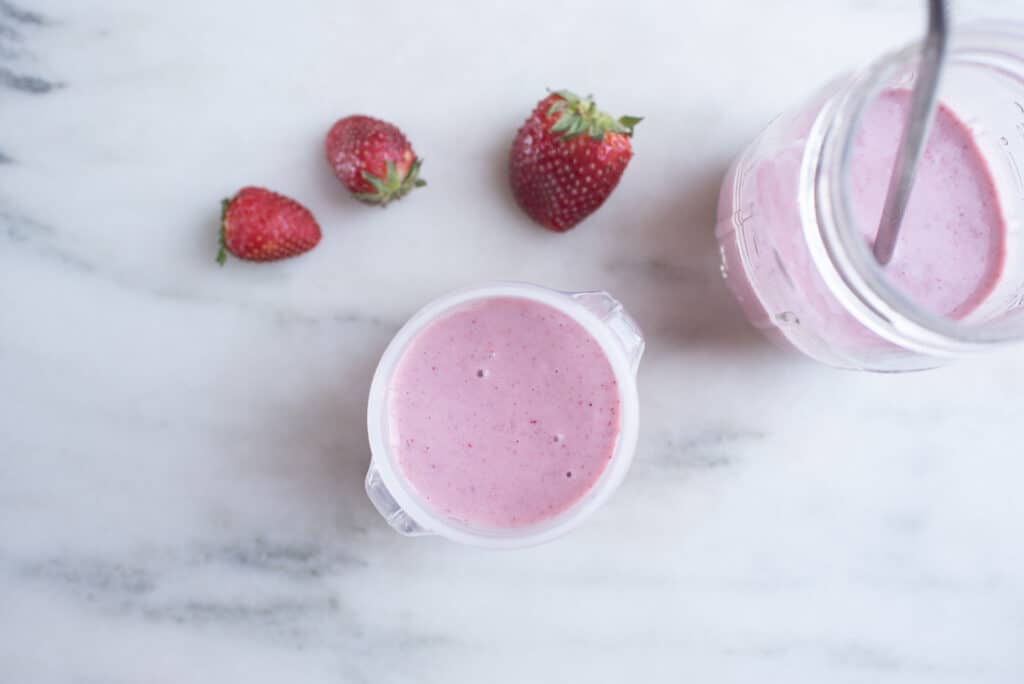 cup of strawberry-hemp seed smoothie with whole strawberries on table next to it
