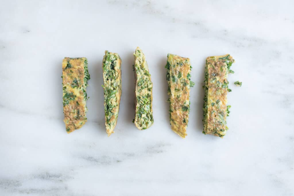 five thin rectangular pieces of kale omelet on a white background