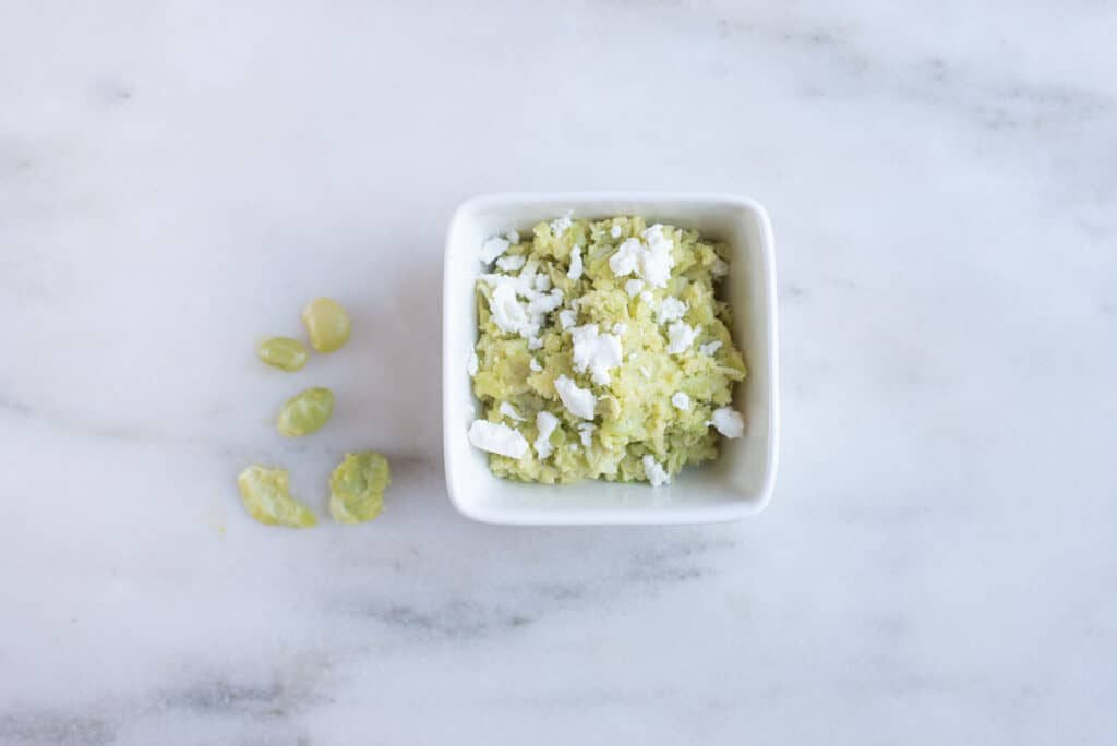 a square bowl filled with cooked, mashed lima beans topped with goat cheese for babies starting solids