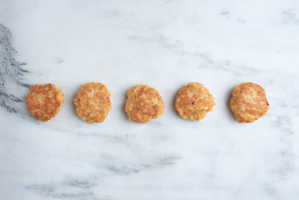five lobster cakes on a countertop