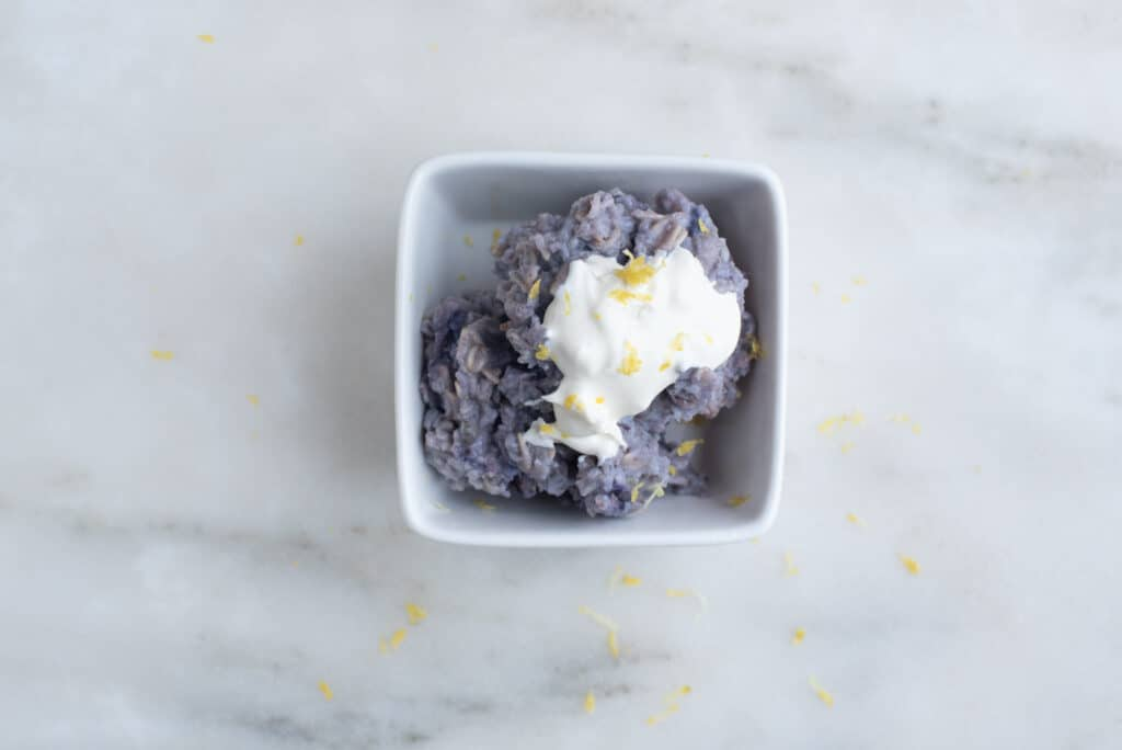 bowl of blueberry oatmeal topped with mascarpone cheese and lemon zest, sitting on a countertop