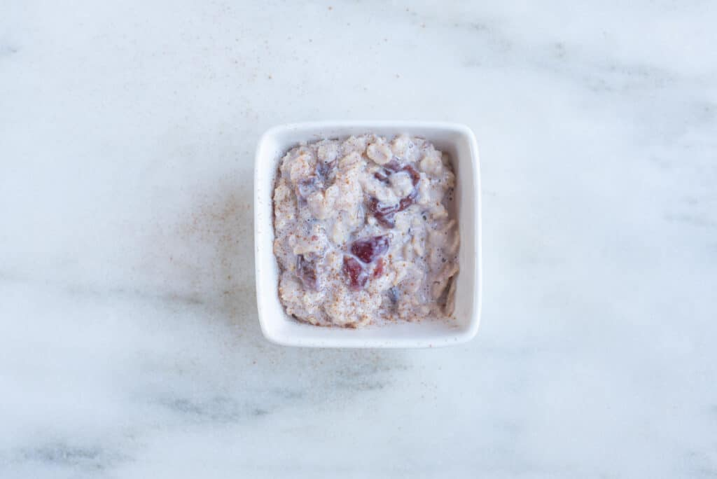 a square bowl filled with oatmeal and fruit cooked with milk for babies starting solids