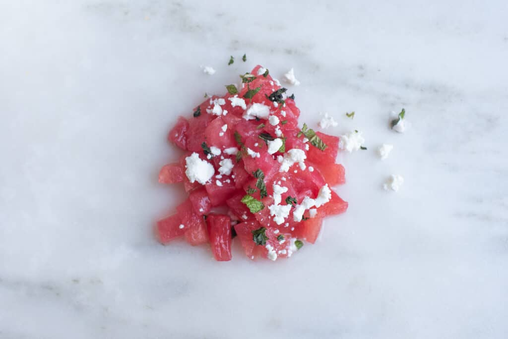bite sized pieces of watermelon sprinkled with goat cheese and finely minced mint, sitting on a countertop