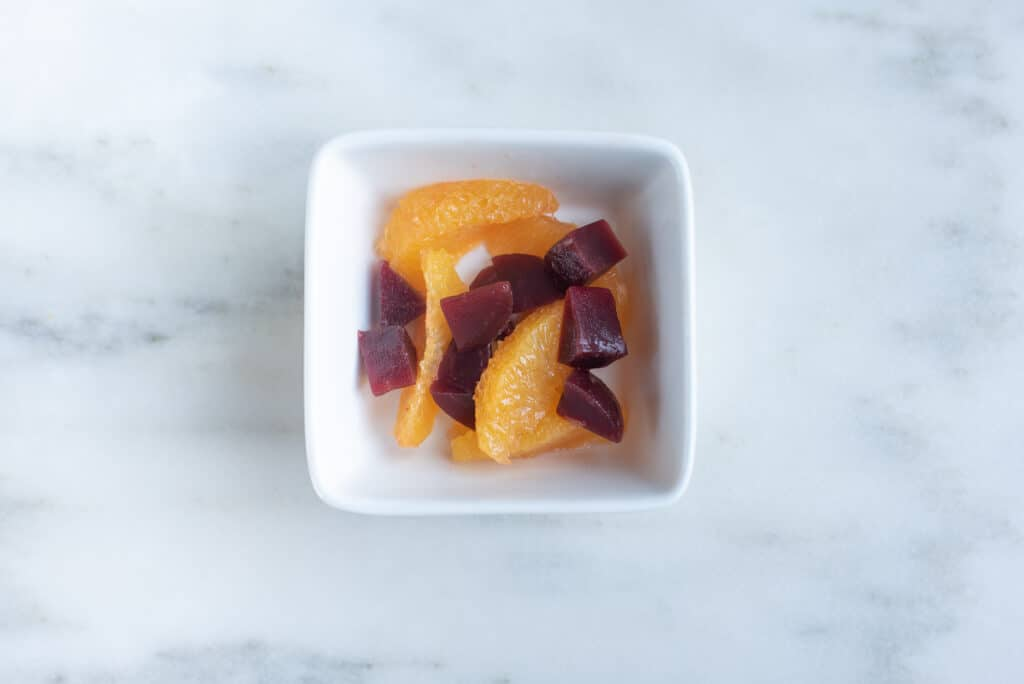 bowl containing pieces of peeled, roasted beets and peeled slices of orange