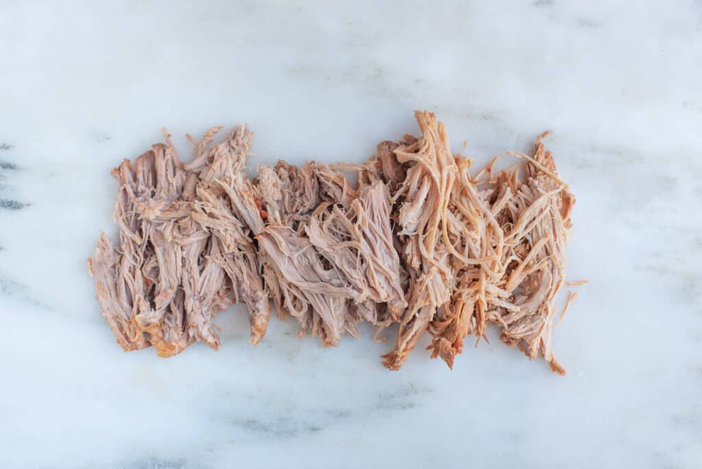 shreds of pulled pork spread out on a white background for babies starting solids
