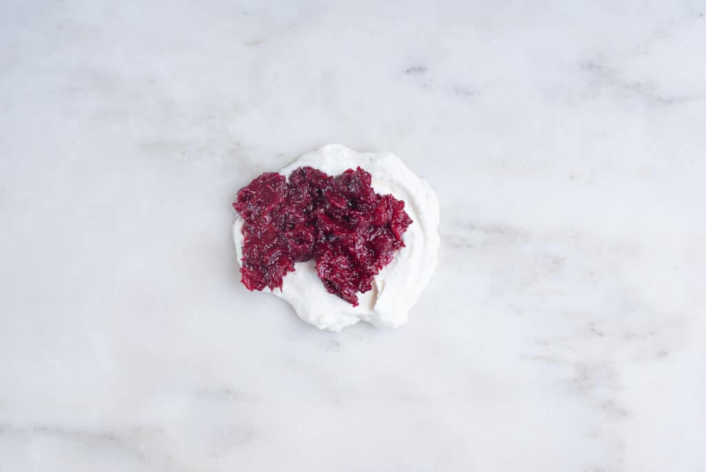pile of ricotta cheese topped with cranberry sauce, sitting on a countertop