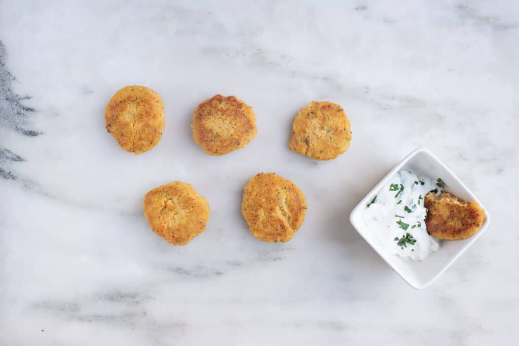 five shrimp cakes on a counter, next to a bowl of Greek yogurt containing herbs and a shrimp cake