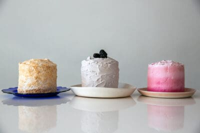 3 birthday cakes side by side, one yellow, one white, one pink