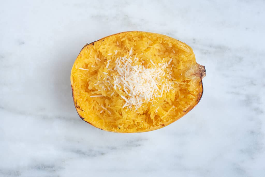 half roasted spaghetti squash, topped with Parmesan cheese, on a countertop