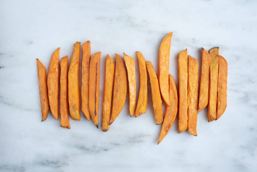 row of peeled, baked sweet potato fries lined up on countertop