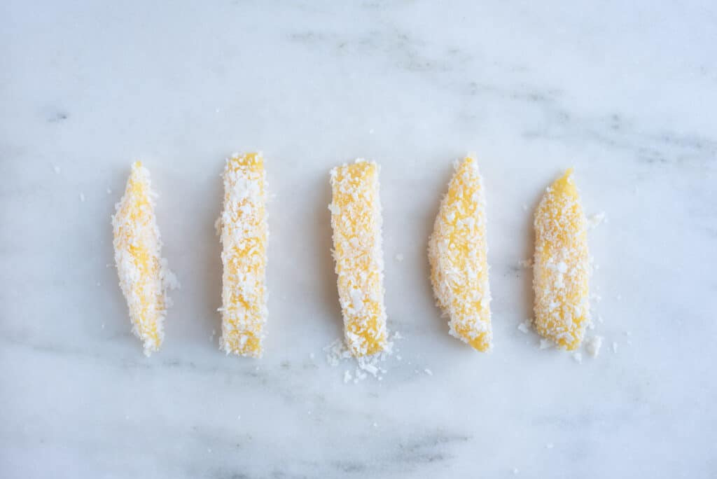 five spears of peeled mango, coated in a tamarind marinade and rolled in coconut flakes