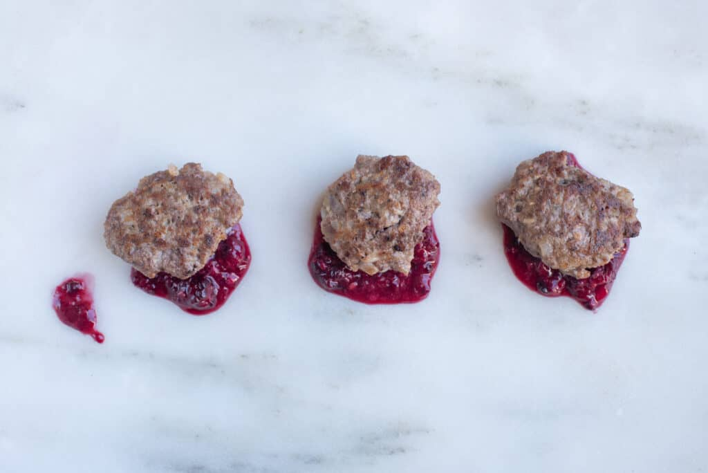 three venison patties on top of dabs of blackberry sauce for babies starting solids