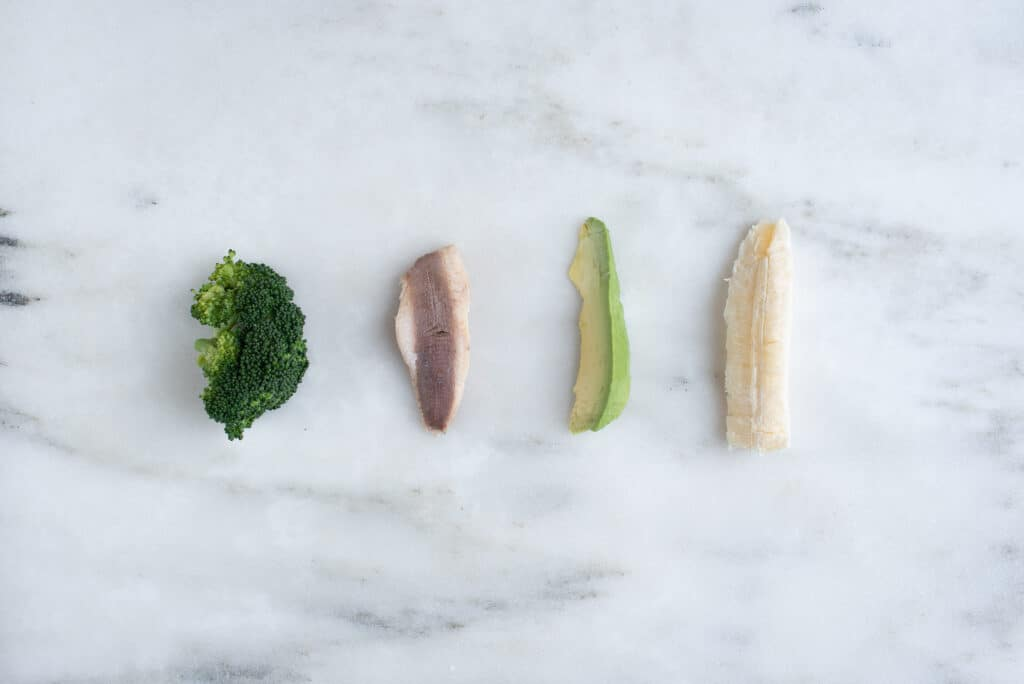 4 pieces of food on a marble counter: steamed broccoli floret, a sardine filet, an avocado spear, and a banana spear.