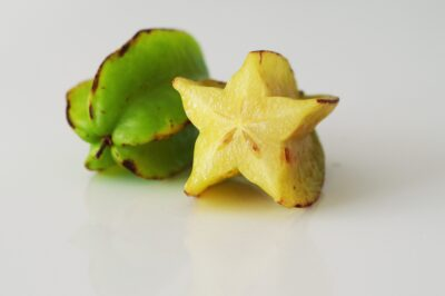 2 star fruits, one yellow and one green, one cut open before being prepared for babies starting solids