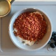 a bowl of strawberry granola, pulverized into a fine meal, with a pitcher of cream on the side