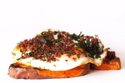 a thin slice of sweet potato topped with a fried egg, quinoa and kale