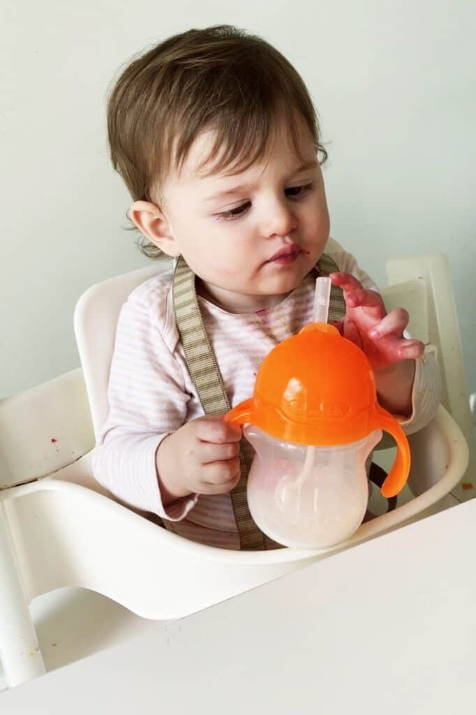 A 13 month old baby inspects the straw on her weighted straw cup