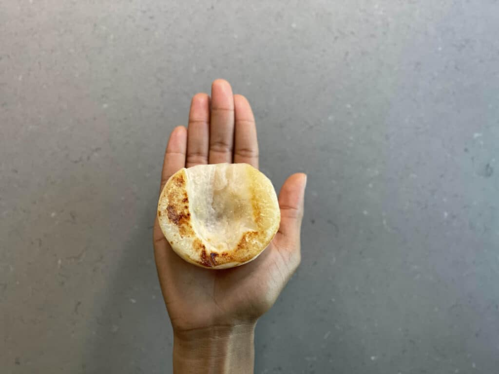 a hand holding half of a cooked Asian pear for babies 6 months+