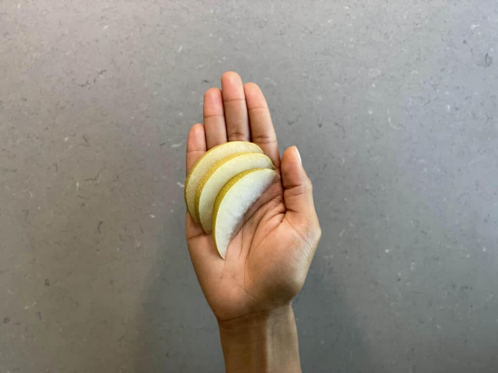 a hand holding paper-thin slices of raw Asian pear for toddlers 12 months+