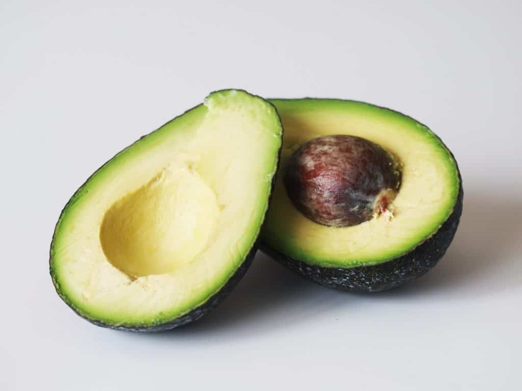 An avocado sliced in half getting prepared for a baby starting solid foods
