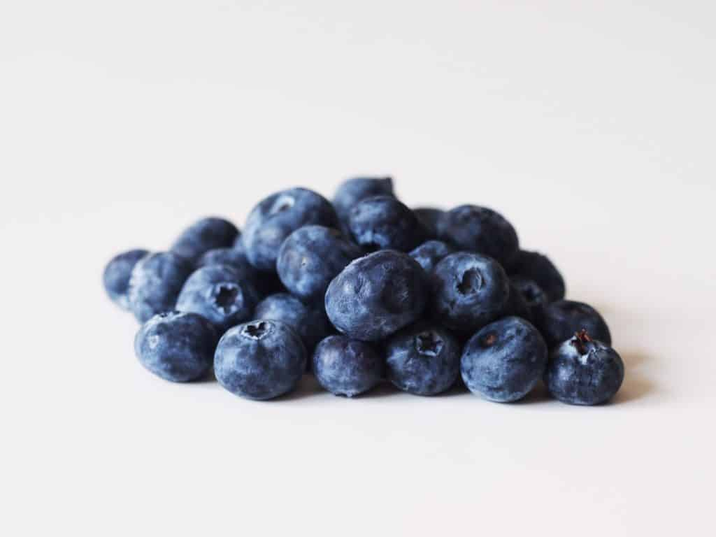 A pile of blueberries before they have been prepared for a baby starting solid foods