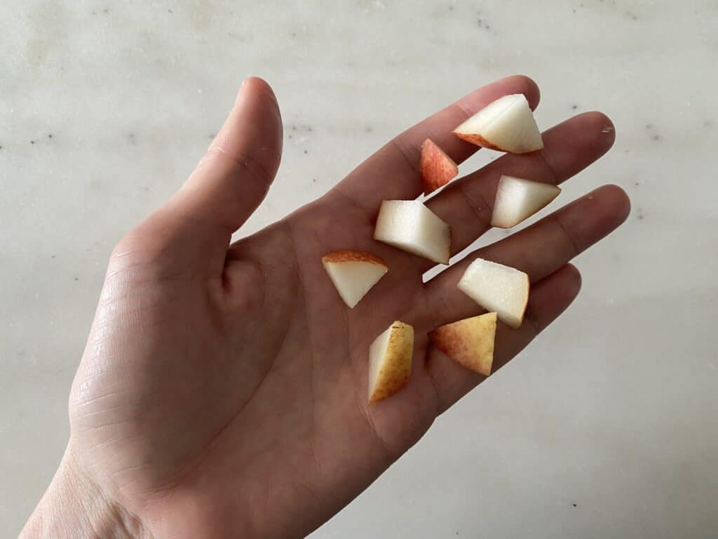 hand holding eight bite size pieces of pear